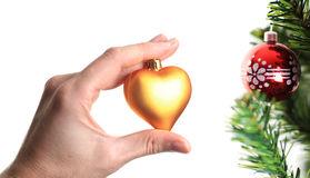 mano-que-adorna-el-árbol-de-navidad-con-el-corazón-de-oro-11766123